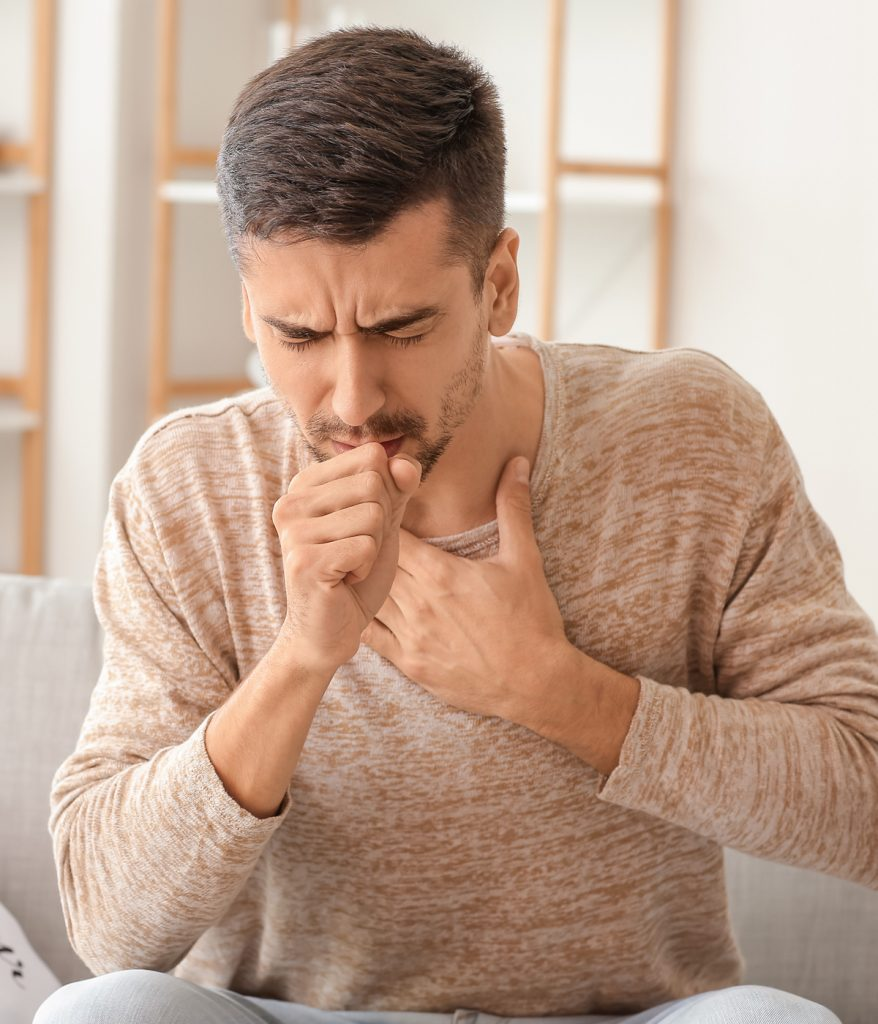 Young man coughing as he holds his chest.