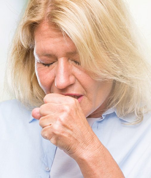 Close up of woman coughing into hand.