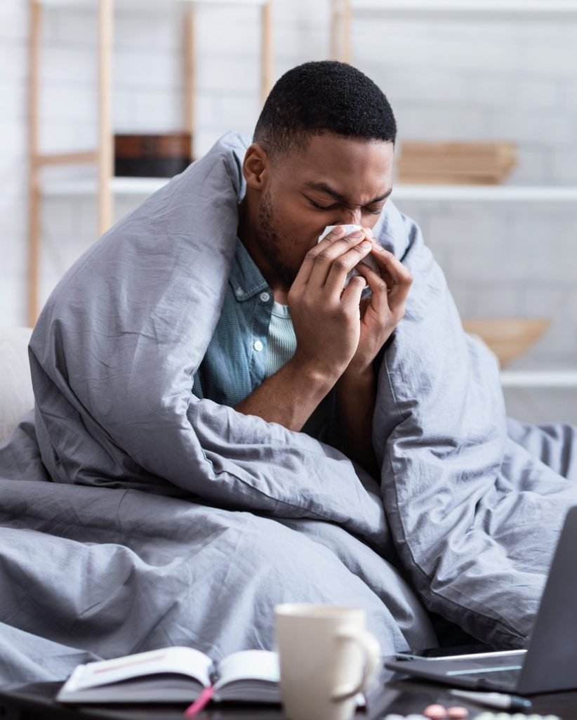 Black man covered with blanket and sneezing into tissue.