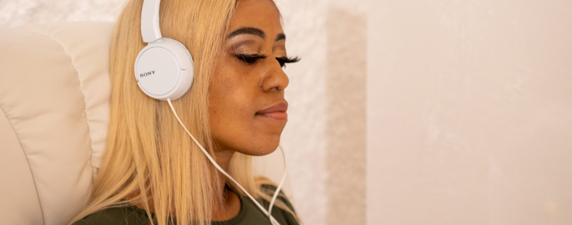 Close up of a black woman with headphones relaxing in a salt room.