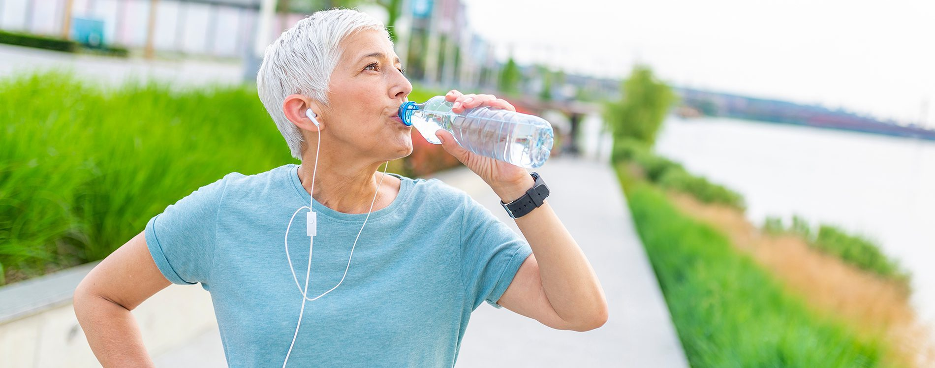 Older person drinking water while exercising.
