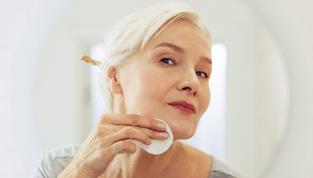 Older woman cleaning her face.