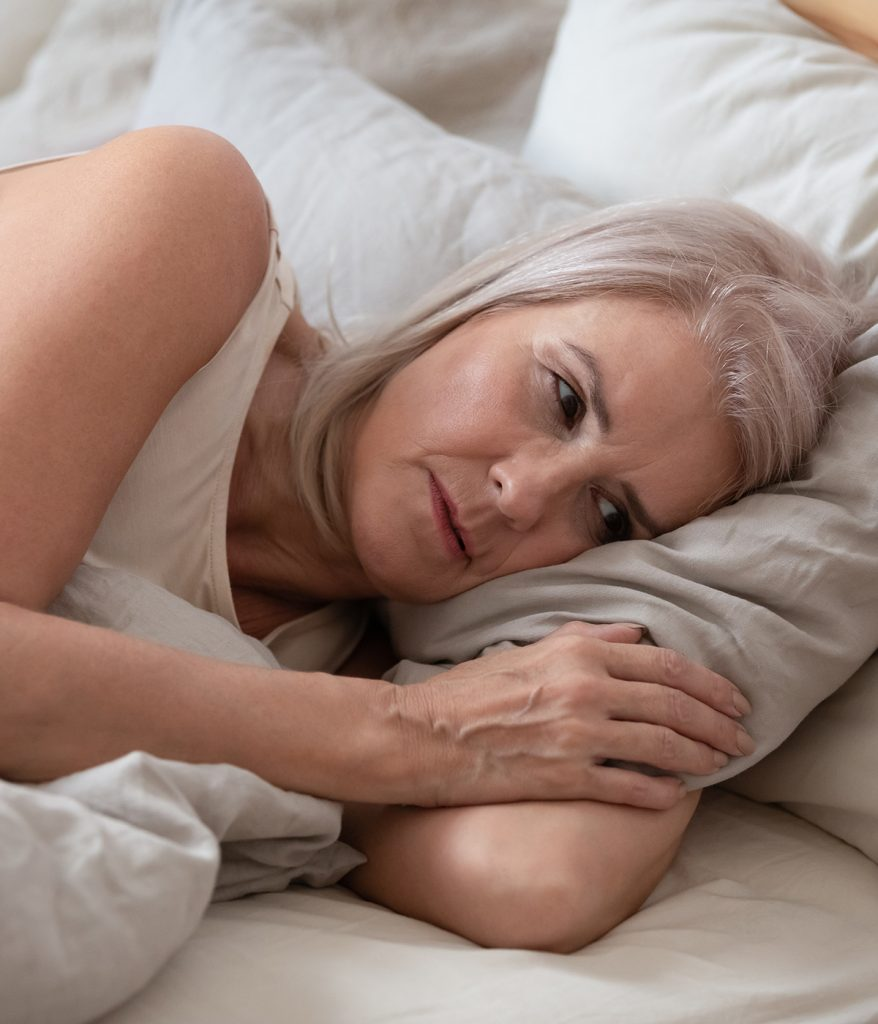 Older woman laying in bed.