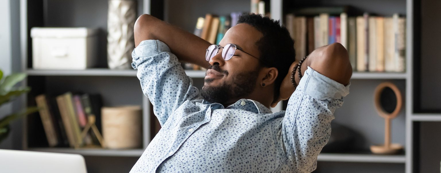 Black man relaxing back in office chair.
