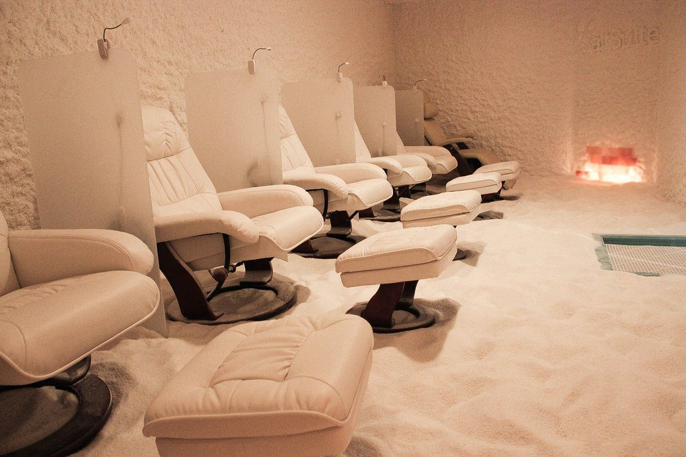 A Salt Suite with leather white chairs, salt on walls and on the floors.
