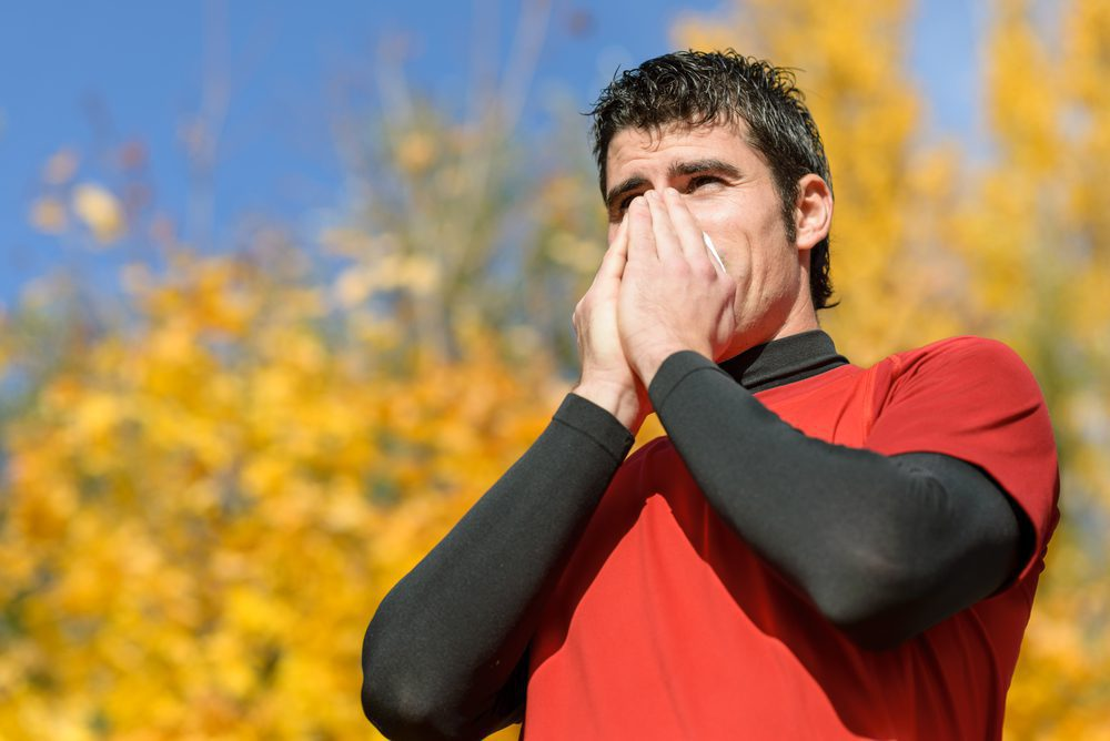 Middle aged man sneezing into tissue as he exercises outside.