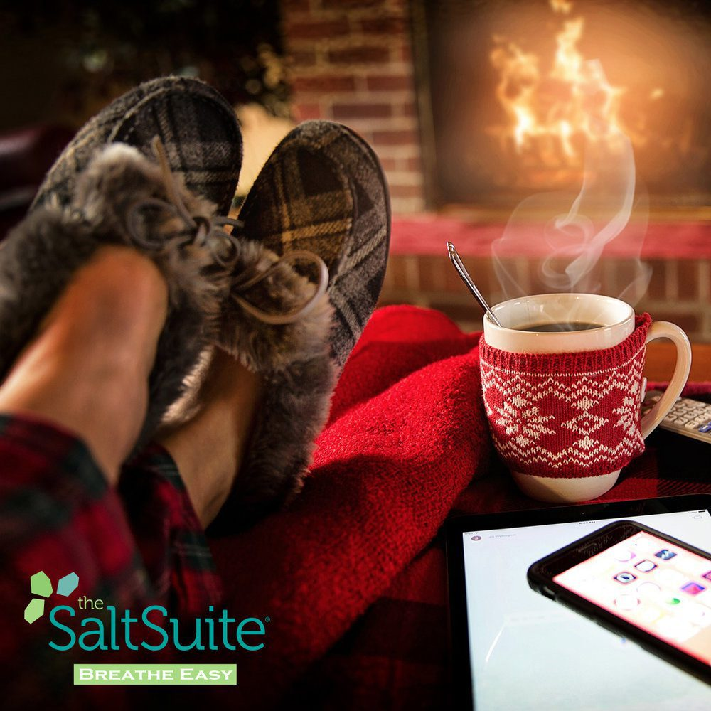 Person relaxing by fireplace and enjoying a cup of coffee during Christmas time.