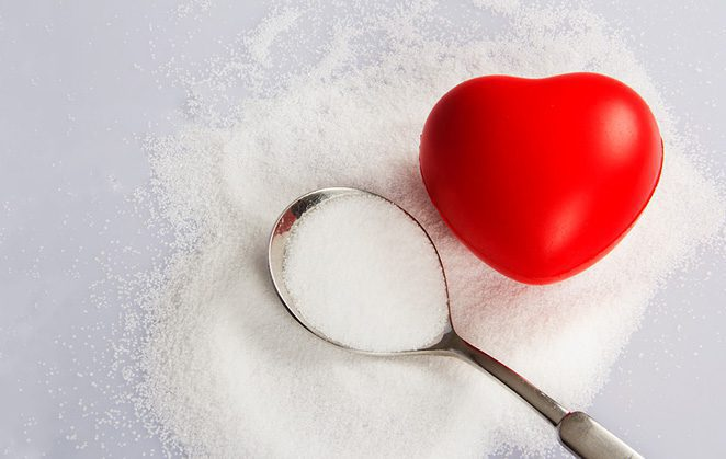 Spoon with salt on a pile of salt with heart shaped stress ball.
