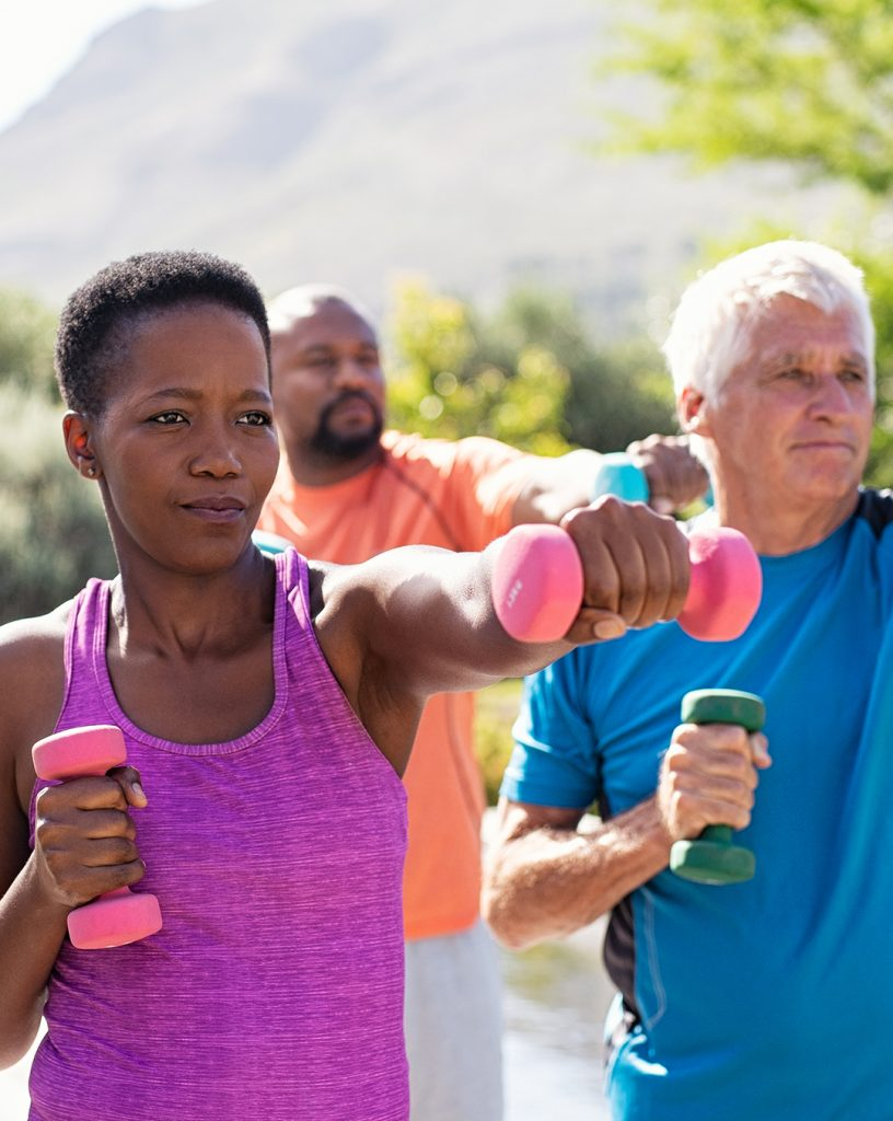 Black middle age woman, black middled age man, and older white man exercising outside.