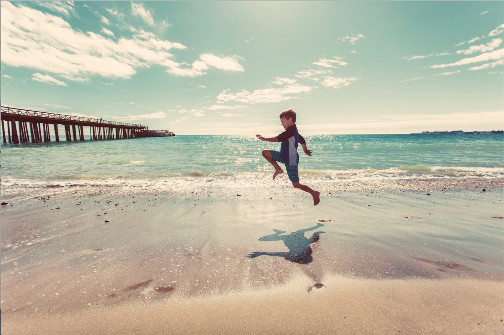 Young boy jumping on the ocean shore by a pier.
