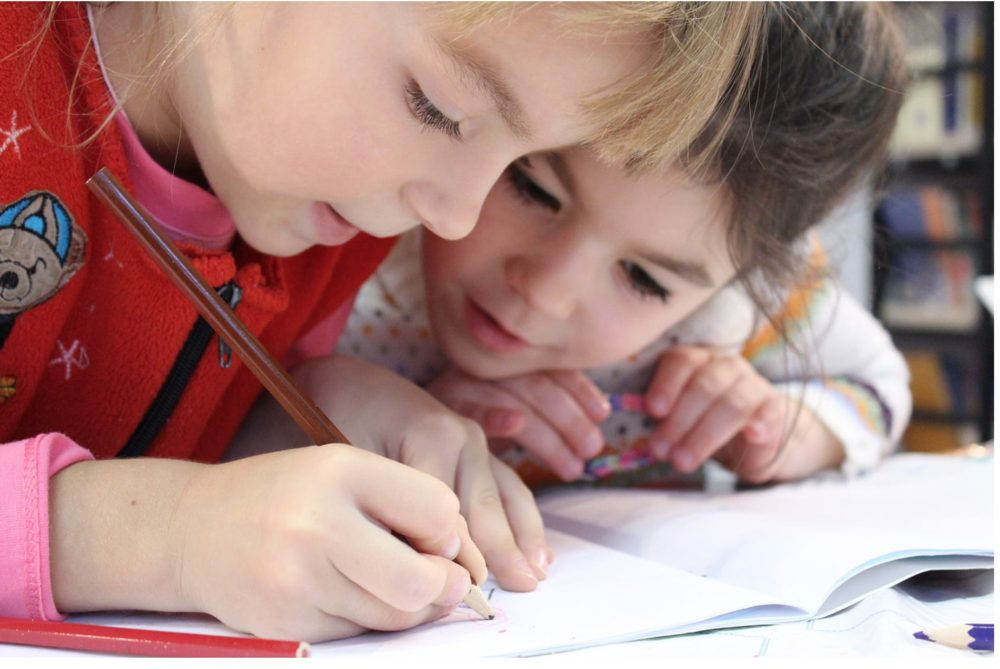 Two little girls side by side at school drawing a picture.