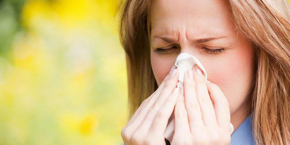 Woman sneezing into tissue while being outdoors.