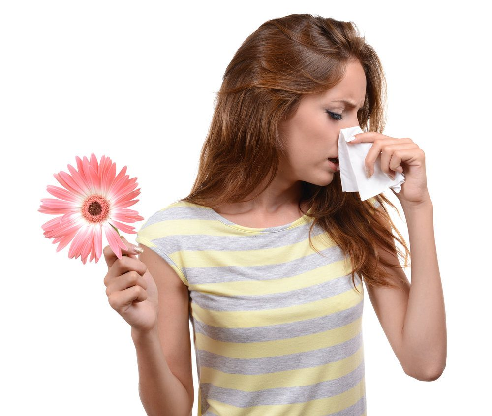 Young woman sneezing on a tissue due to a flower being held on her right hand.