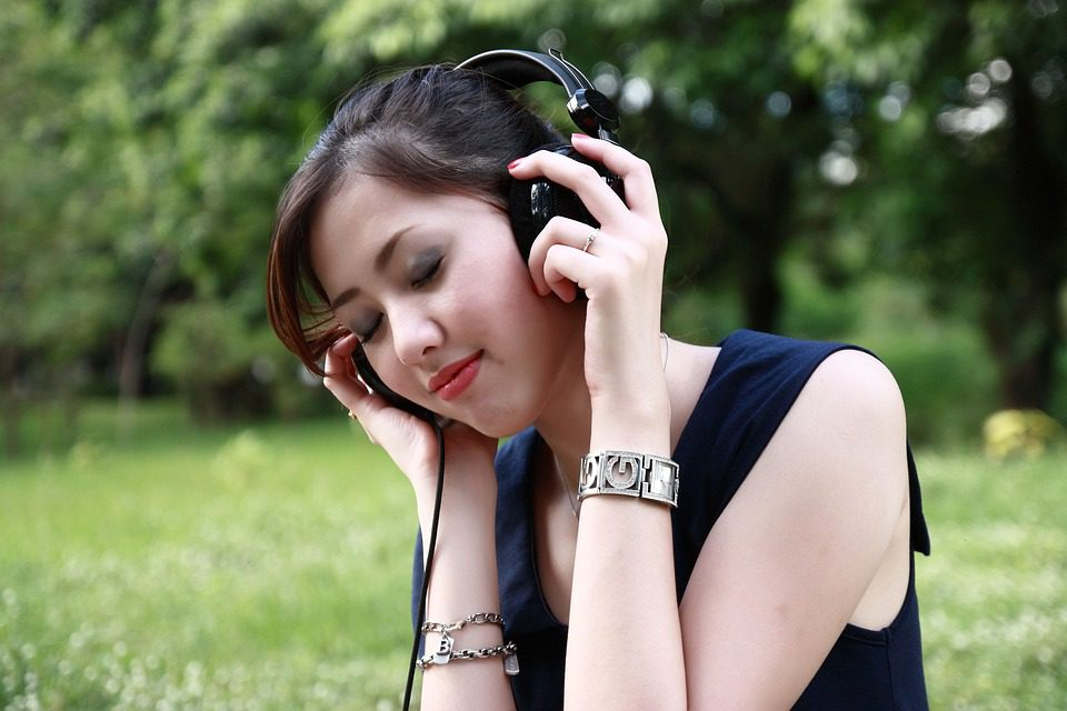 Asian woman enjoying the outdoors with headphones on.