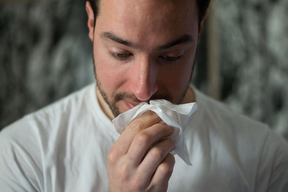 Middle aged man wiping nose with tissue.