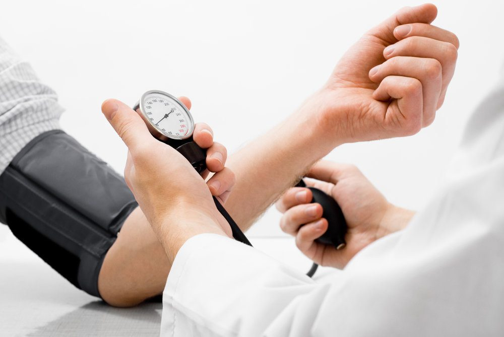 Doctor checking patient's blood pressure manually.