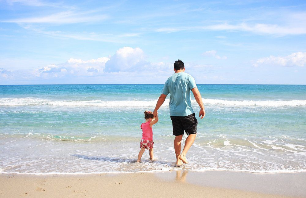 Father holding daughters hand as they walk on ocean shore.