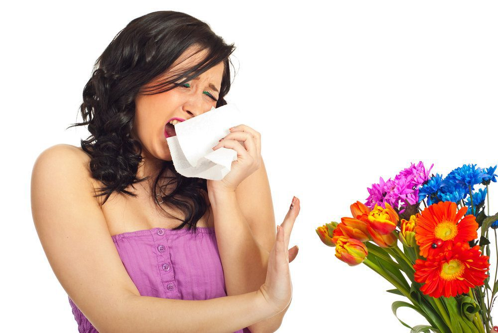Young pretty women sneezing and rejecting flowers given to her due to allergies.