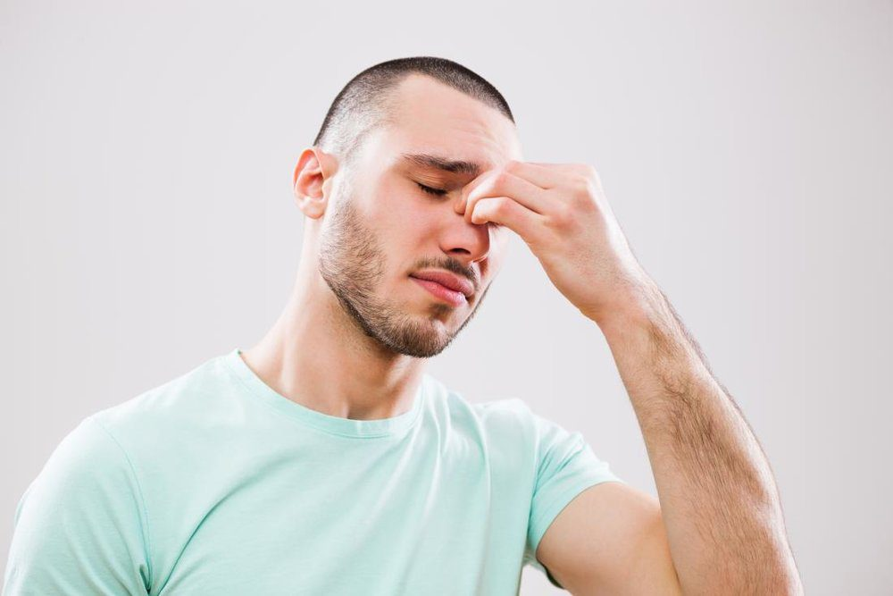 Young man with headache and sinusitis applying pressure on nose and sinus areas.