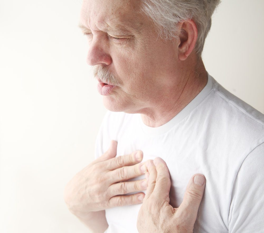 Older man with his hands on his chest and exhaling.