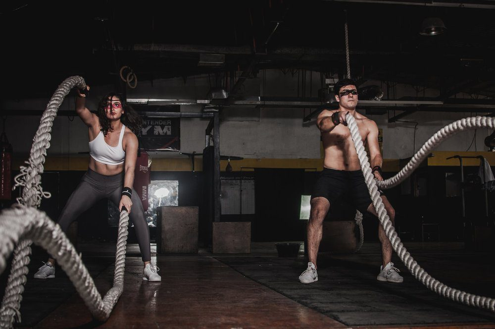 Man and woman doing crossfit battle ropes.