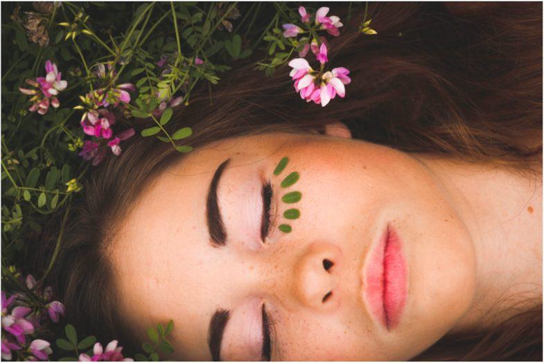 Young pretty woman laying on bed of flowers.